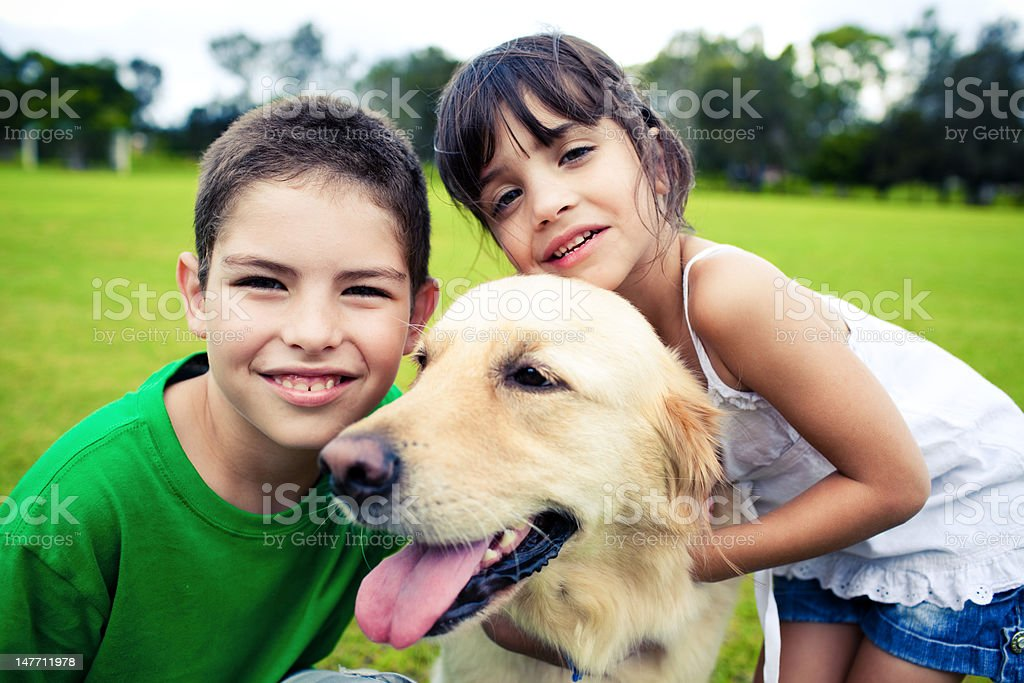 Young boy and girl hugging a golden retriever royalty-free stock photo