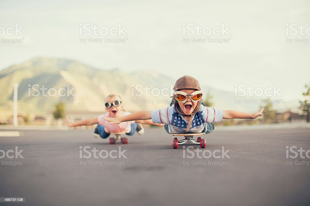 A young boy and girl are wearing flying goggles while outstretching...