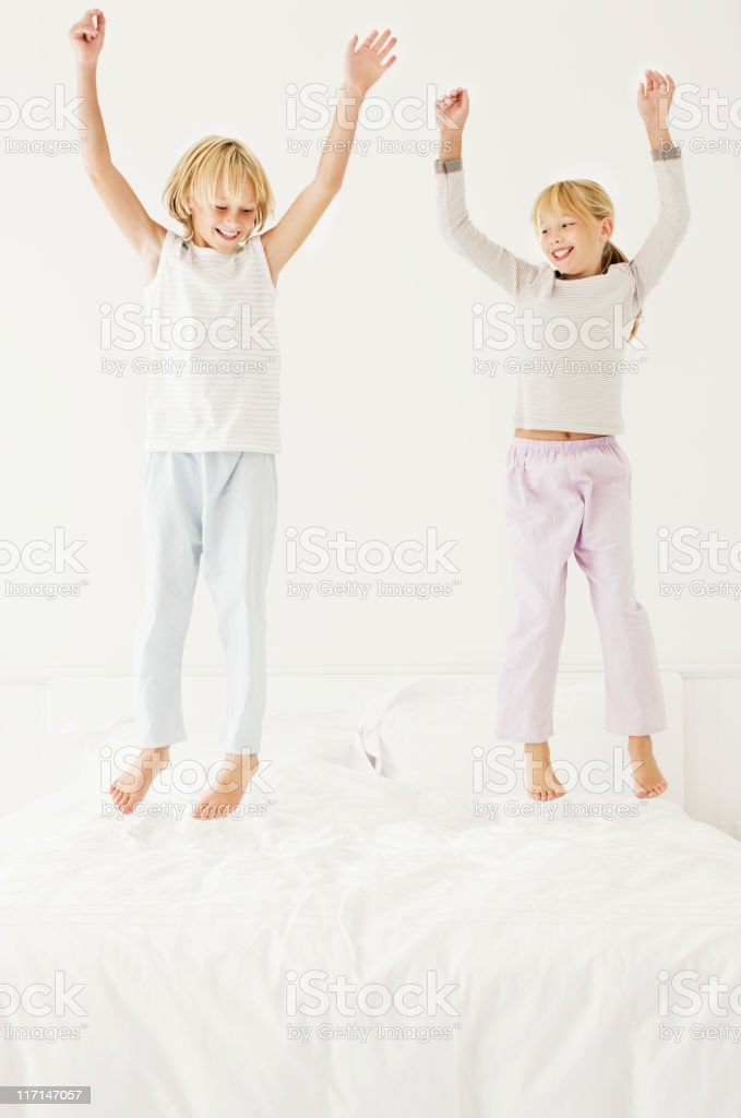 Young Boy and Girl Jumping on the Bed royalty-free stock photo