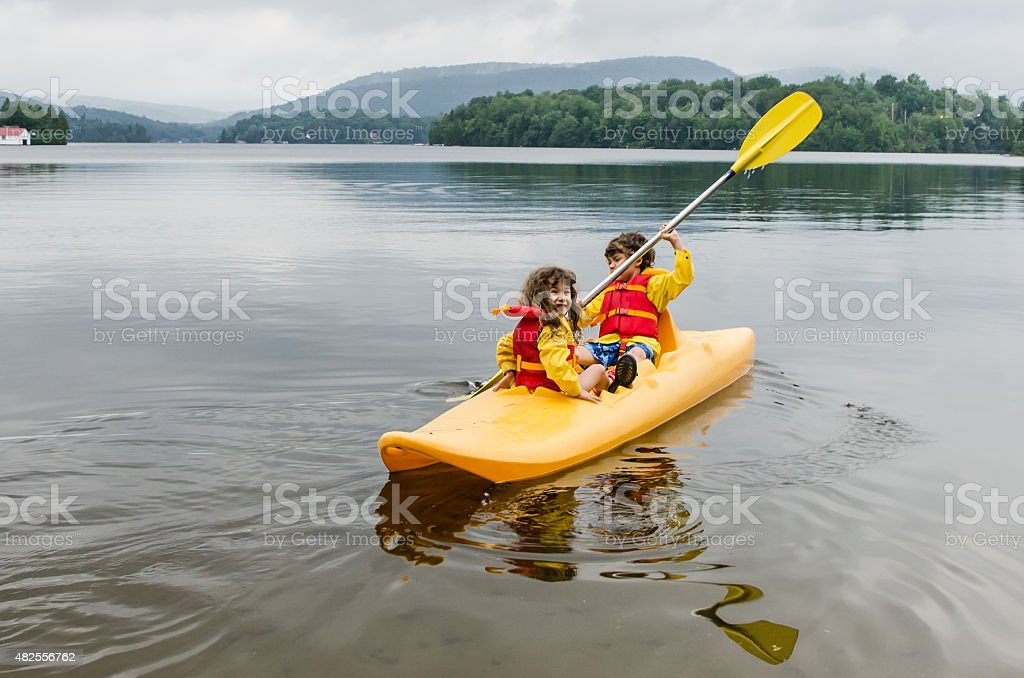Young boy and girl kayaking on a lake stock photo