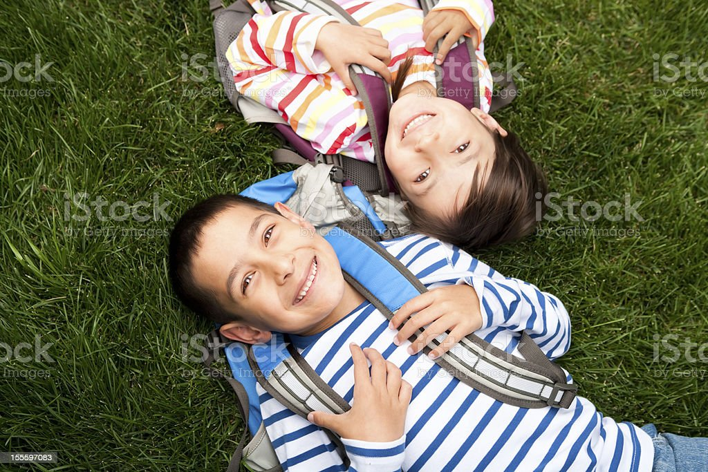 Young boy and girl laying in the grass at school stock photo