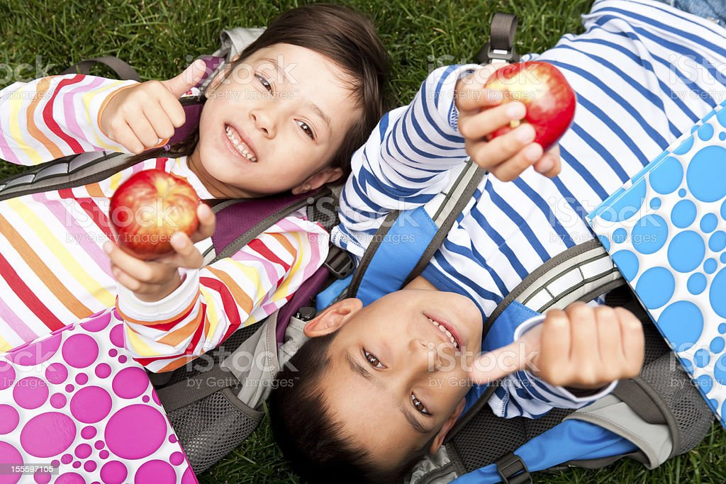 Young boy and girl laying with an apple royalty-free stock photo