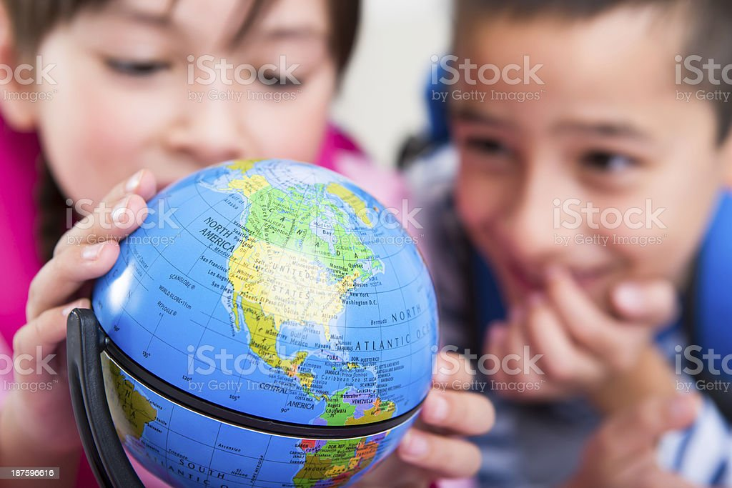 Young boy and girl looking at the globe royalty-free stock photo