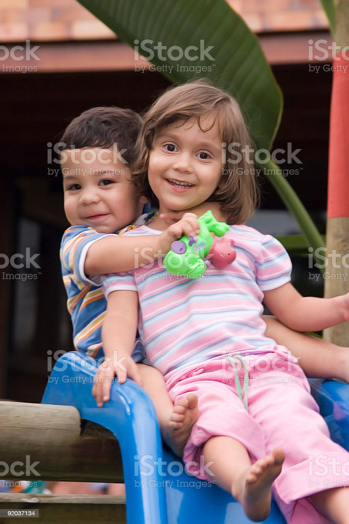A young boy and girl on a slide royalty-free stock photo