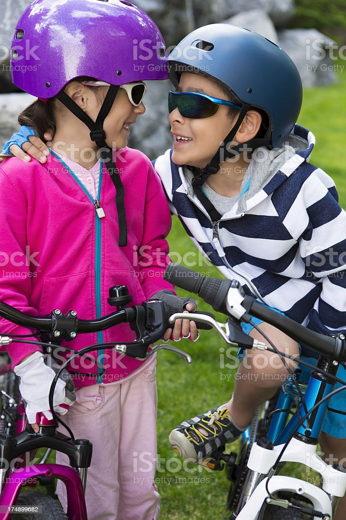 Young boy and girl on their bikes talking royalty-free stock photo
