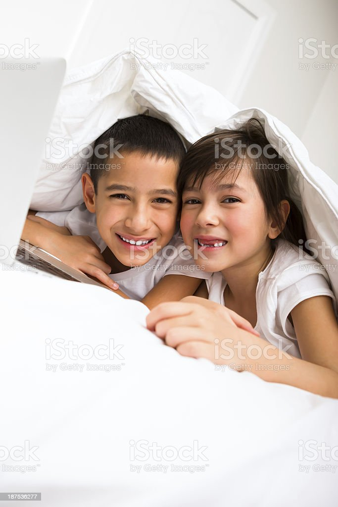 Young boy and girl playing on a laptop royalty-free stock photo
