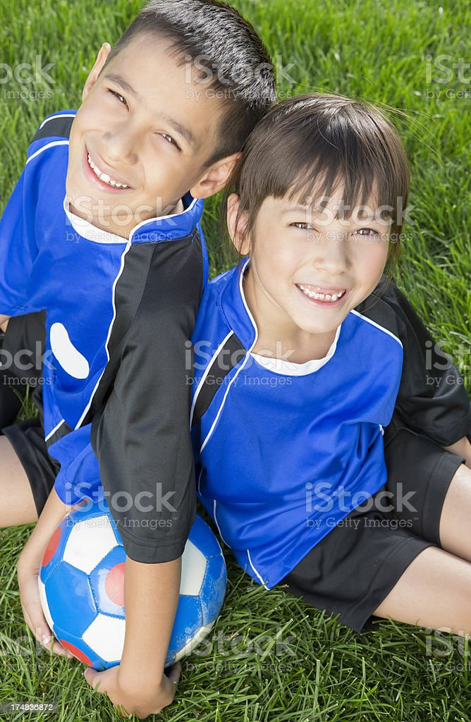 Young boy and girl resting on the soccer field royalty-free stock photo