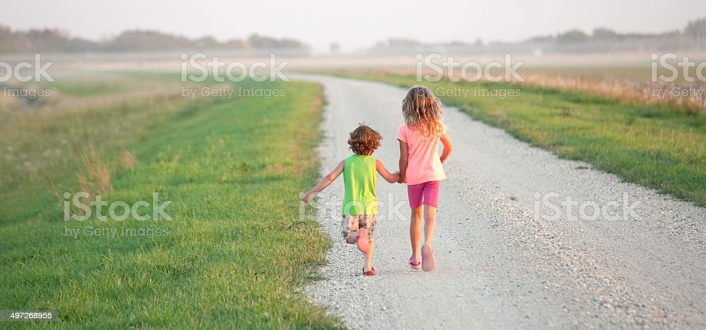Young Boy and Girl Running Down Gravel Road royalty-free stock photo
