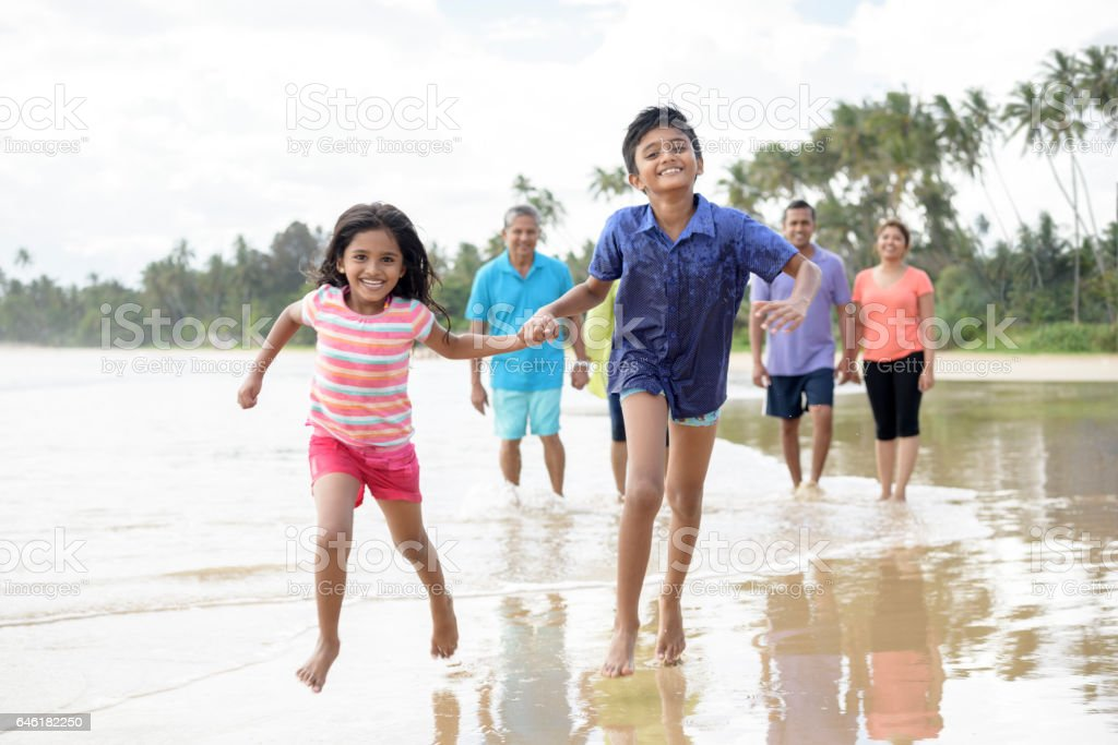 Young boy and girl running on beach holding hands stock photo