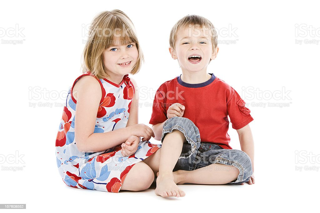 Young boy and girl sitting back to back on white royalty-free stock photo