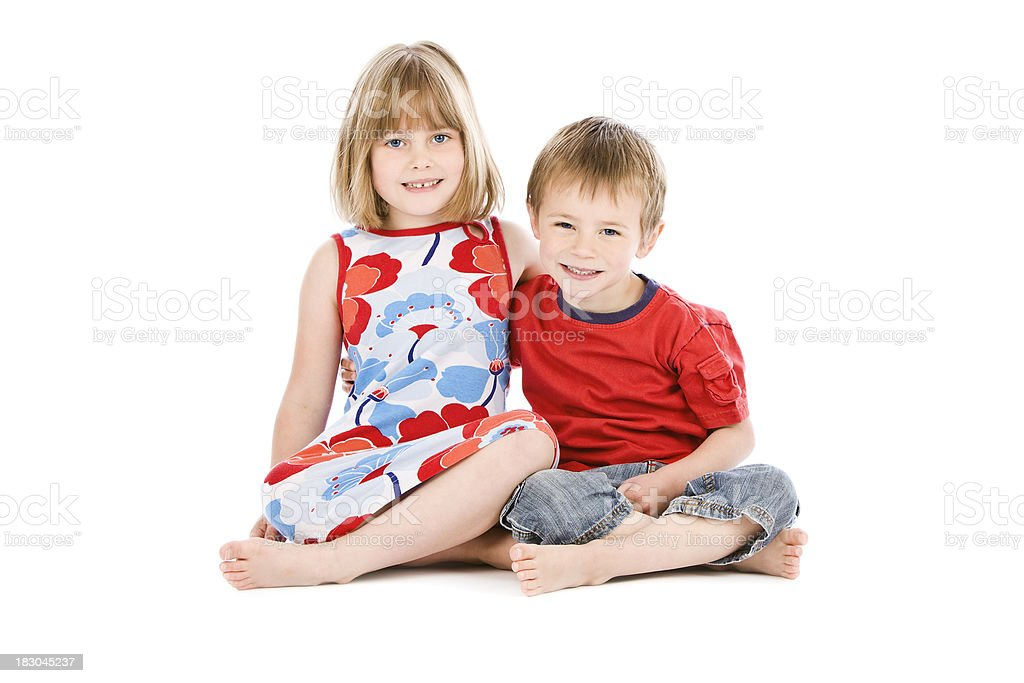 Young boy and girl sitting on white background royalty-free stock photo