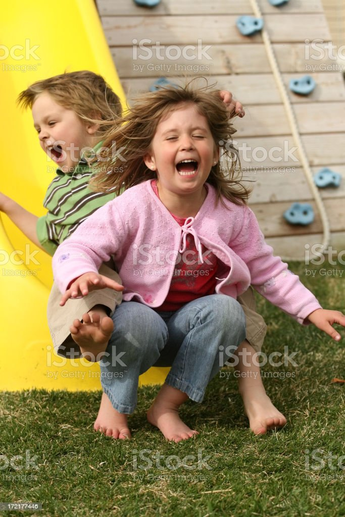 Young Boy And Girl Sliding Off Slide royalty-free stock photo