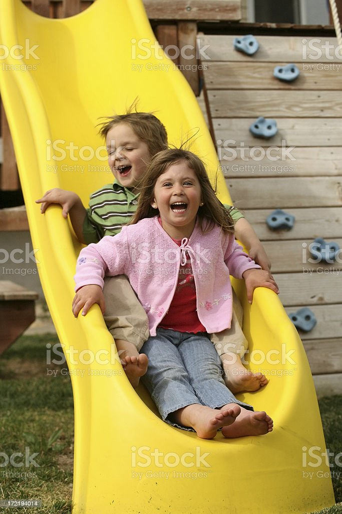 Young Boy And GIrl Sliding On The Slide Grining royalty-free stock photo