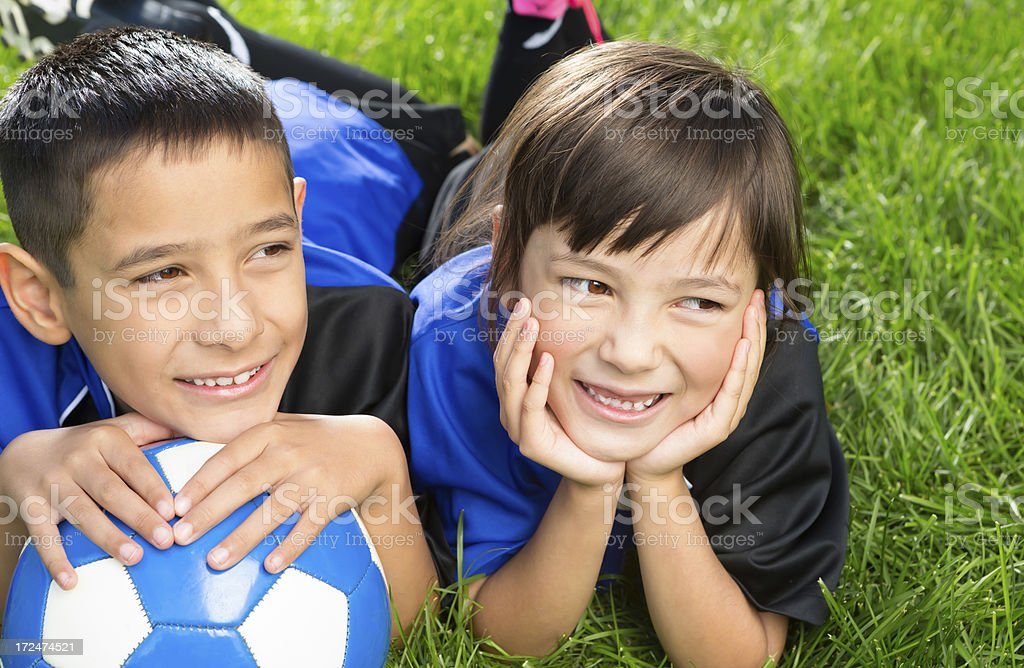 Young boy and girl taking a break from soccer royalty-free stock photo