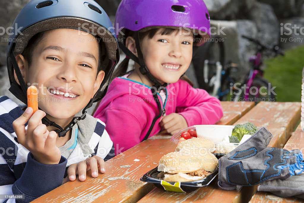 Young boy and girl taking a break to eat royalty-free stock photo