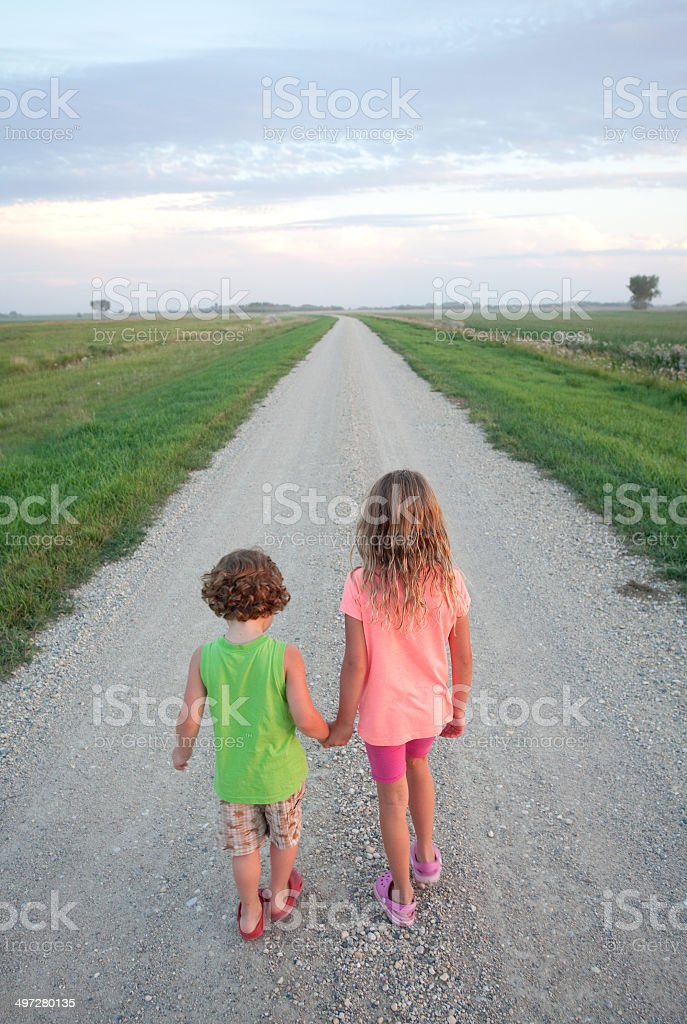 Young Boy and Girl Walking Down Gravel Road royalty-free stock photo
