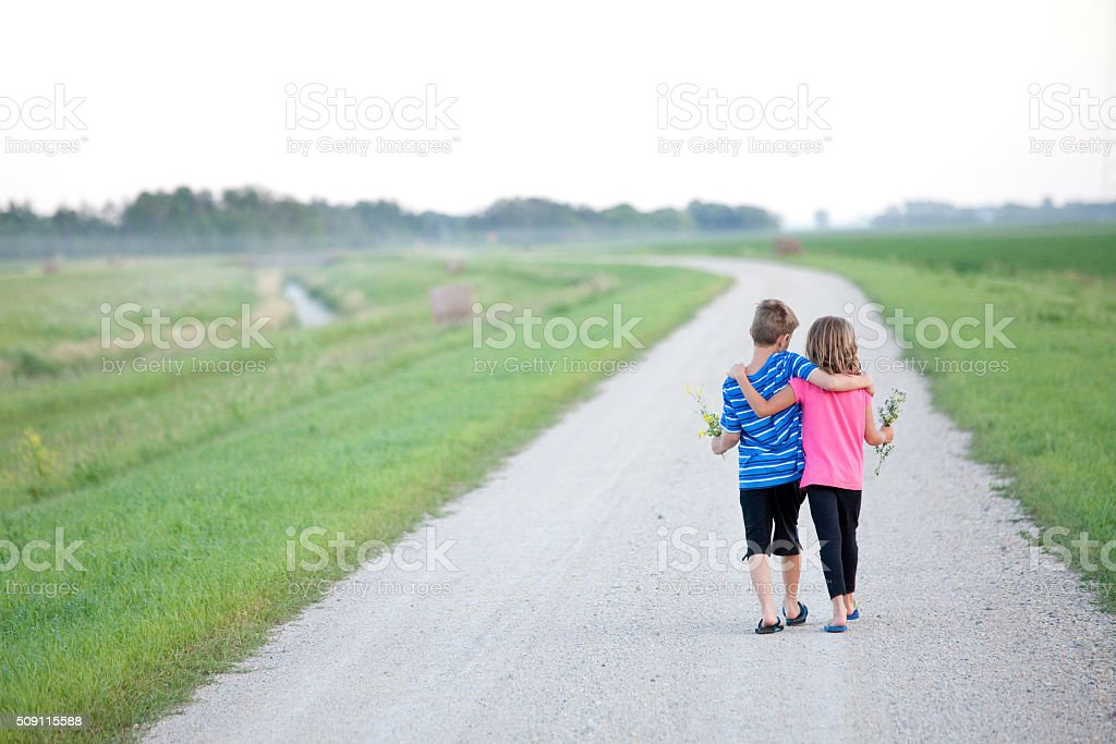 Young Boy and Girl Walking Down Gravel Road stock photo