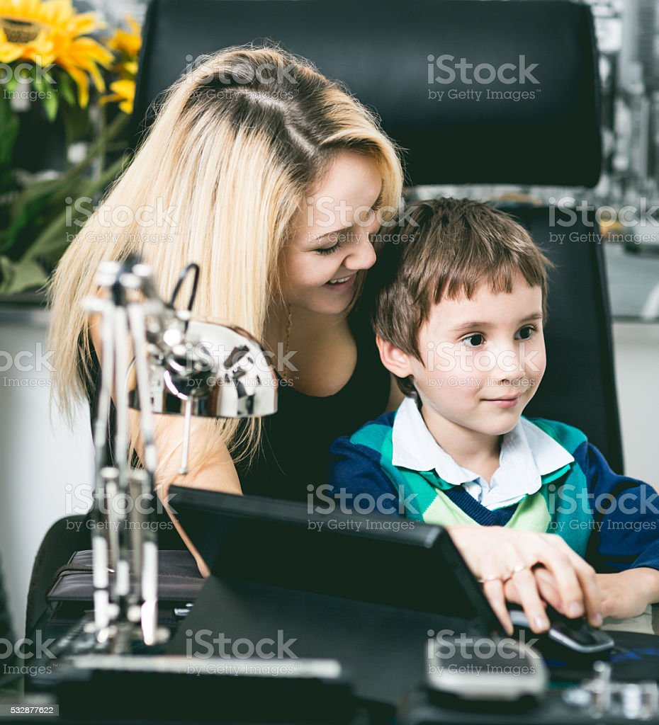 Young boy and her mom on the computer table stock photo