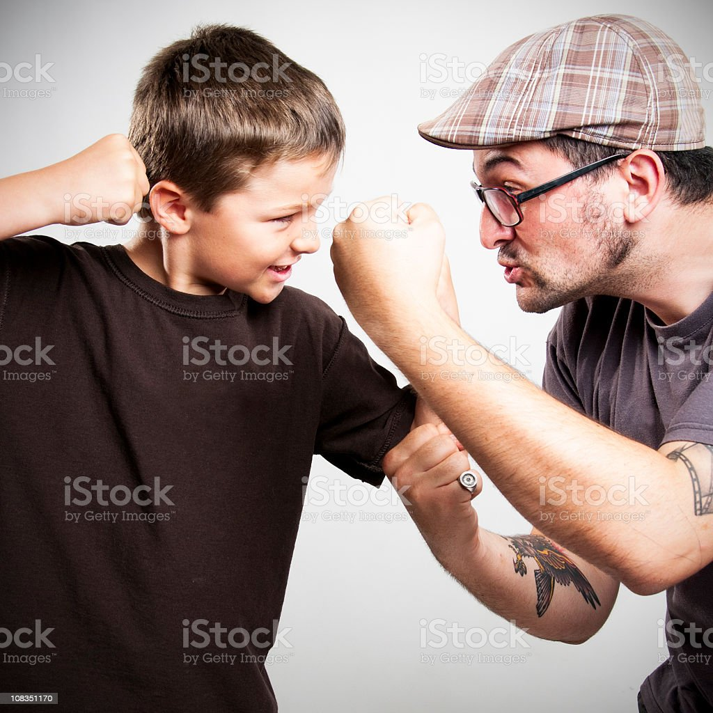 Young boy and man play fighting royalty-free stock photo