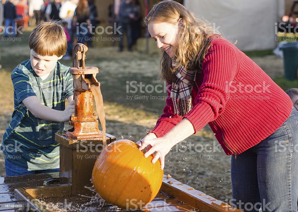 Young boy and mother cleaning pumpkins at a pumpkin patch royalty-free stock photo