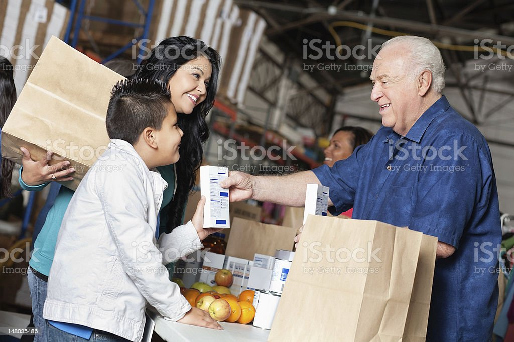 Young boy and mother donating food at a pantry royalty-free stock photo
