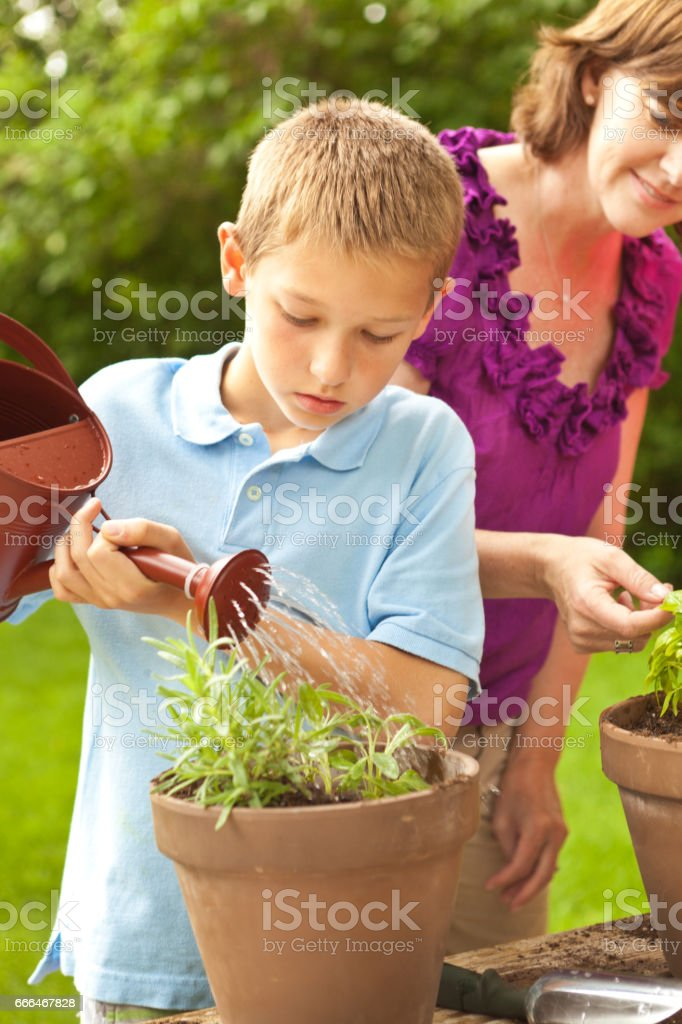 Young Boy and Mother Home Gardening, Planting flowers in pot stock photo