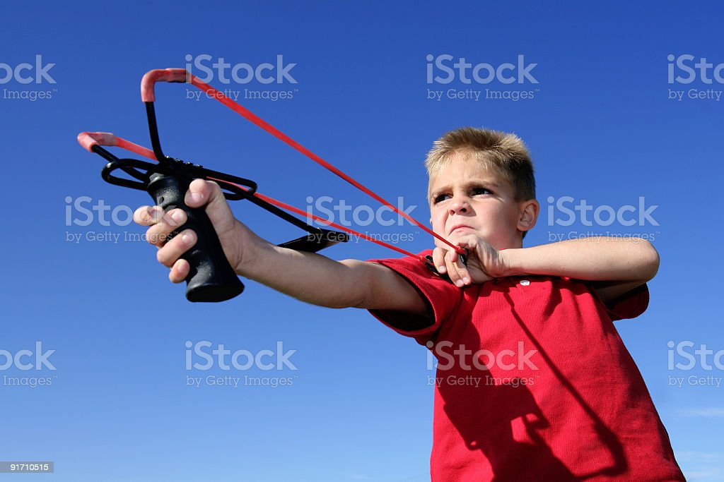Young boy and slingshot stock photo