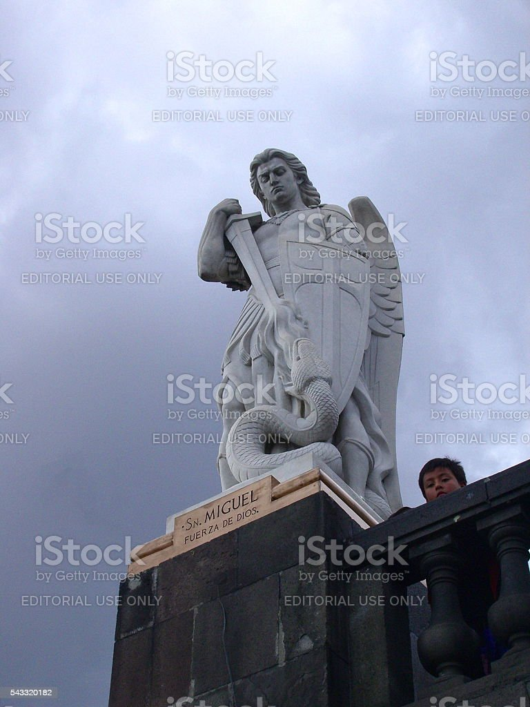 Young boy and statue of St. Michael at Guadalupe stock photo