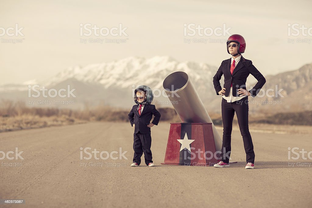 Young Boy and Woman Business Team with Human Cannon stock photo