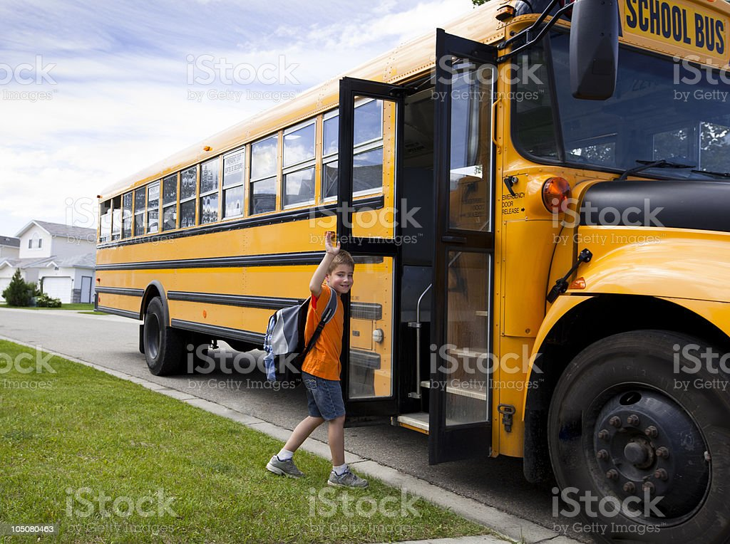 Young boy and yellow school bus stock photo