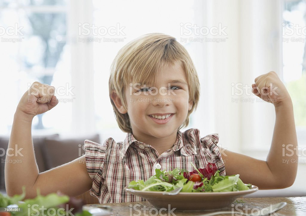 Young boy at dining room table flexing stock photo