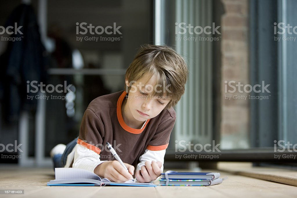 Young boy at home concentrating hard on his homework royalty-free stock photo