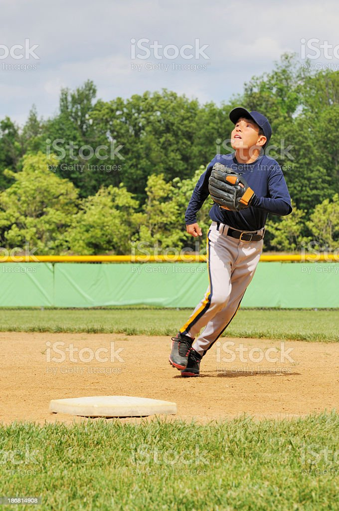 Young Boy Athlete Baseball Player on Field at First Base stock photo