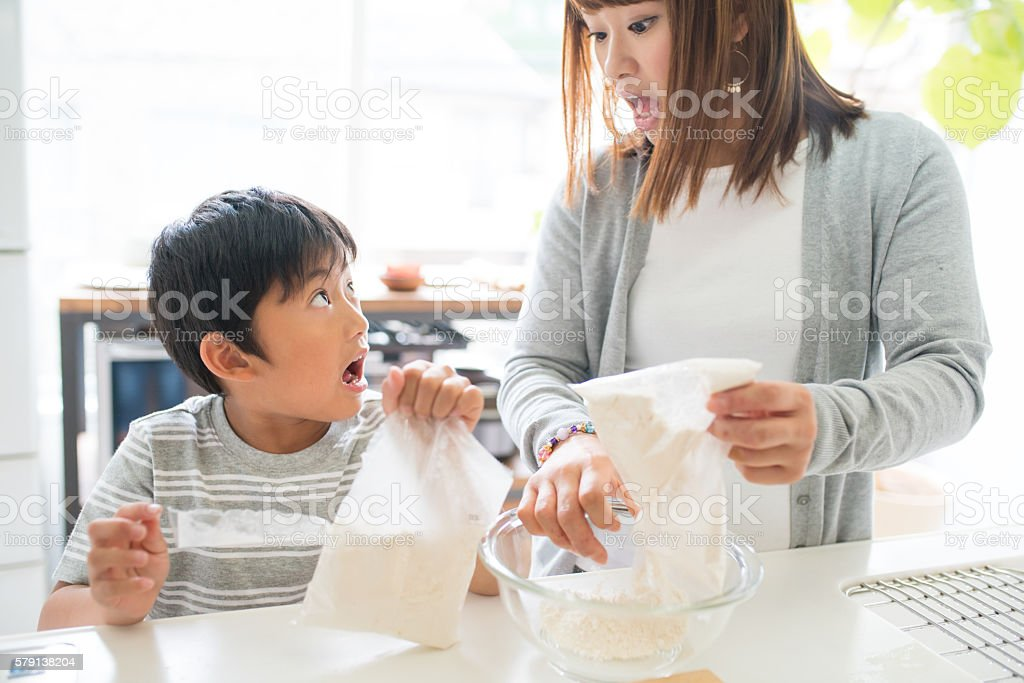 Young boy baking with his mother stock photo