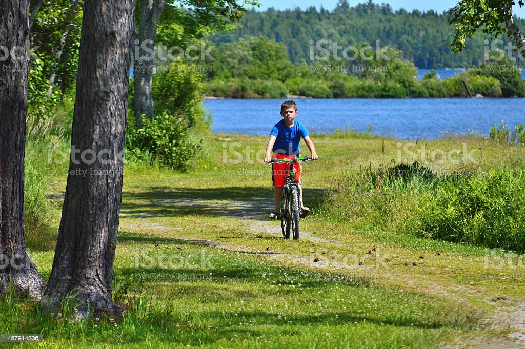 Young Boy Bikes Down Path stock photo