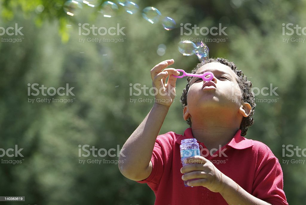 Young boy blowing bubbles outdoors at the park stock photo