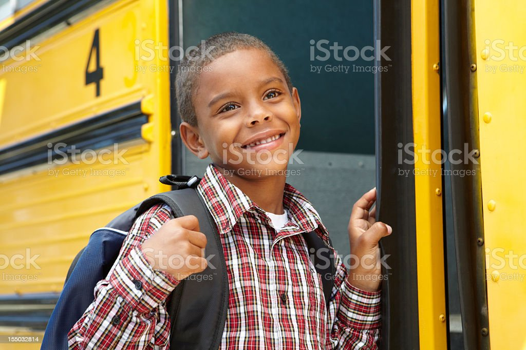 Young boy boarding a yellow school bus with his backpack royalty-free stock photo
