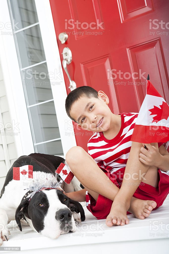 Young boy bonding with his dog on Canada Day royalty-free stock photo