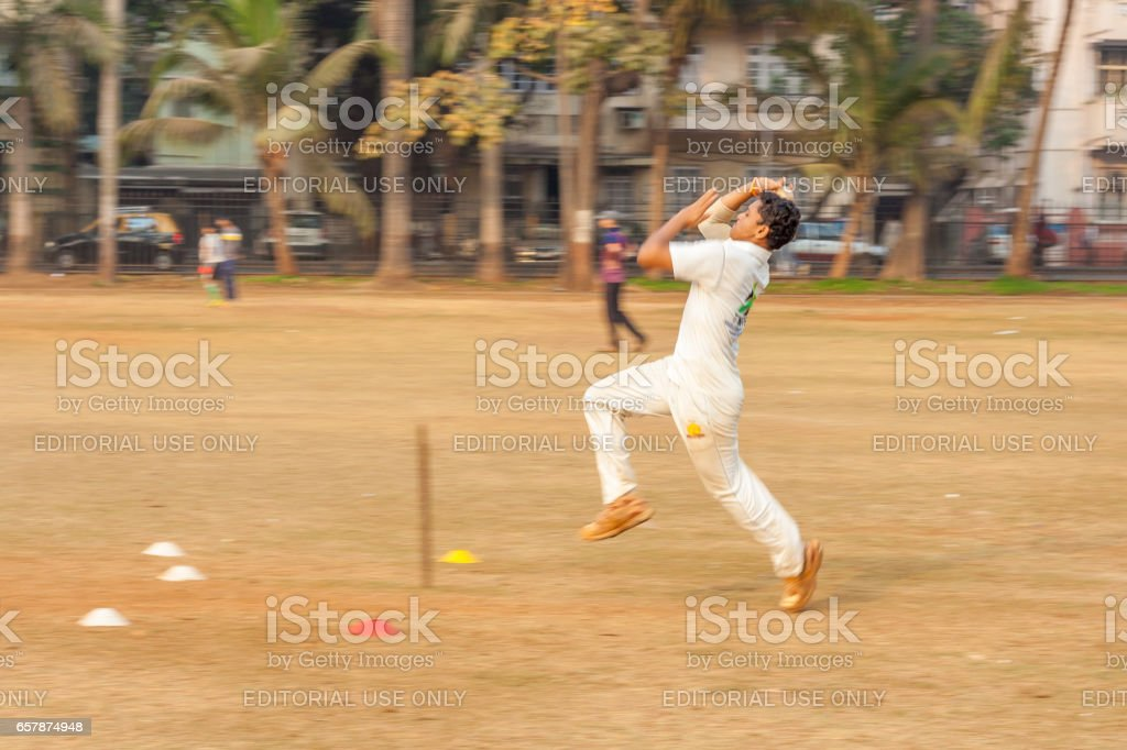 A young Boy bowling at Cricket net stock photo
