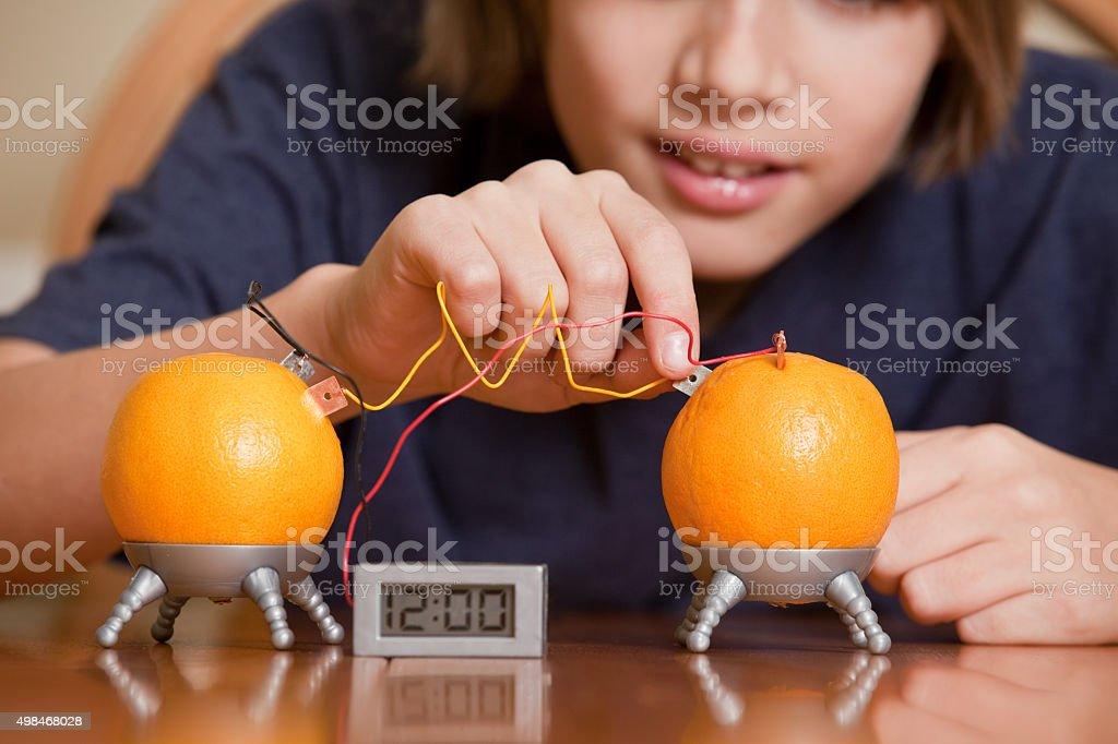 Young Boy Building Fruit Powered clock stock photo