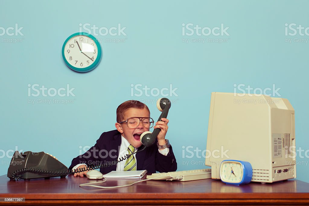 Young Boy Businessman Angrily Yells into the Phone stock photo
