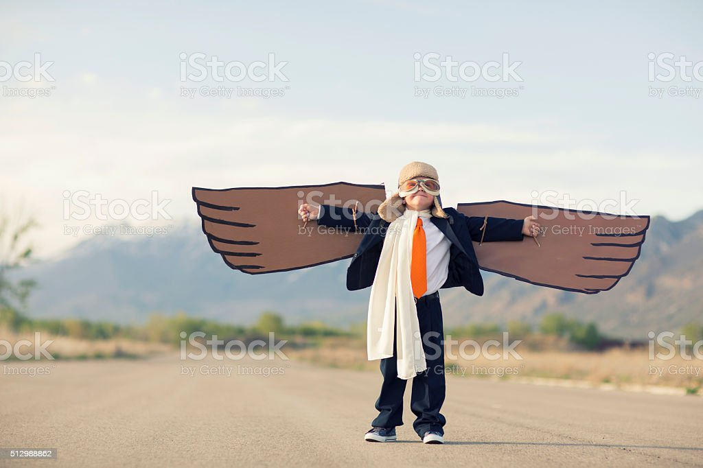 Young Boy Businessman Dressed in Suit with Cardboard Wings stock photo