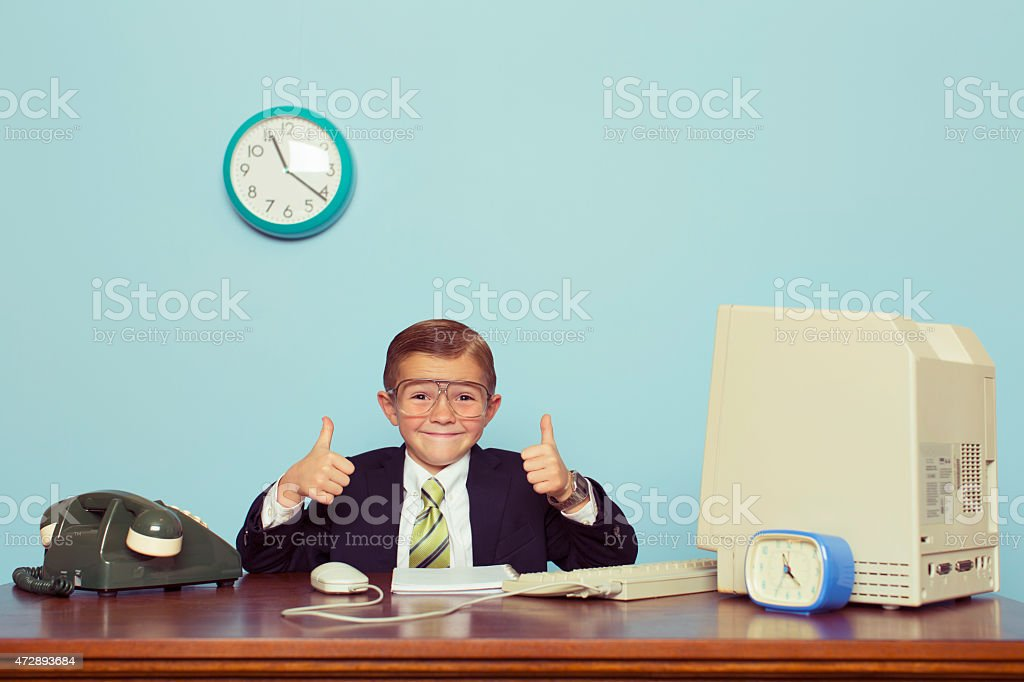 Young Boy Businessman Gives Thumbs Up at Office stock photo