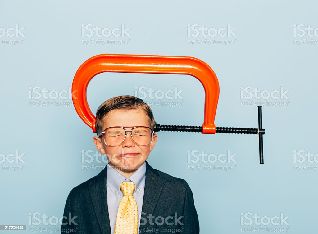 Young Boy Businessman In Pain with Vice on His Head stock photo