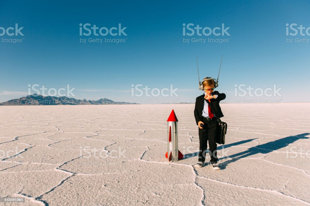 Young Boy Businessman Launching Rocket stock photo