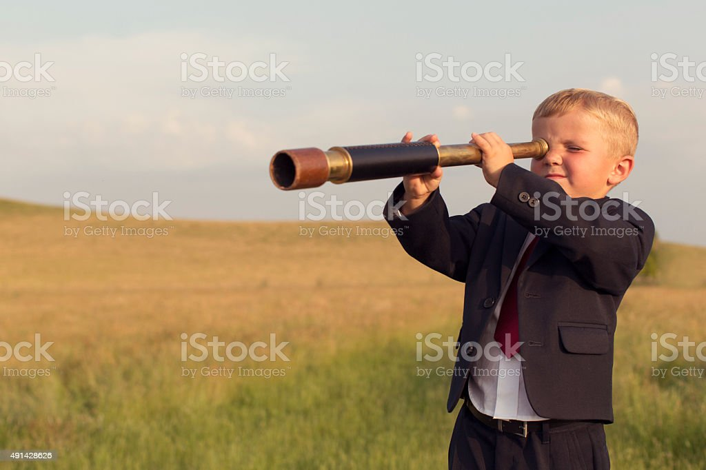 Young Boy Businessman Looking through Telescope stock photo