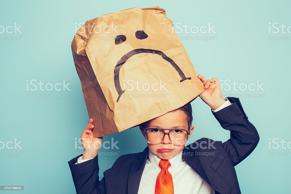 Young Boy Businessman Puts a Sad Face On stock photo