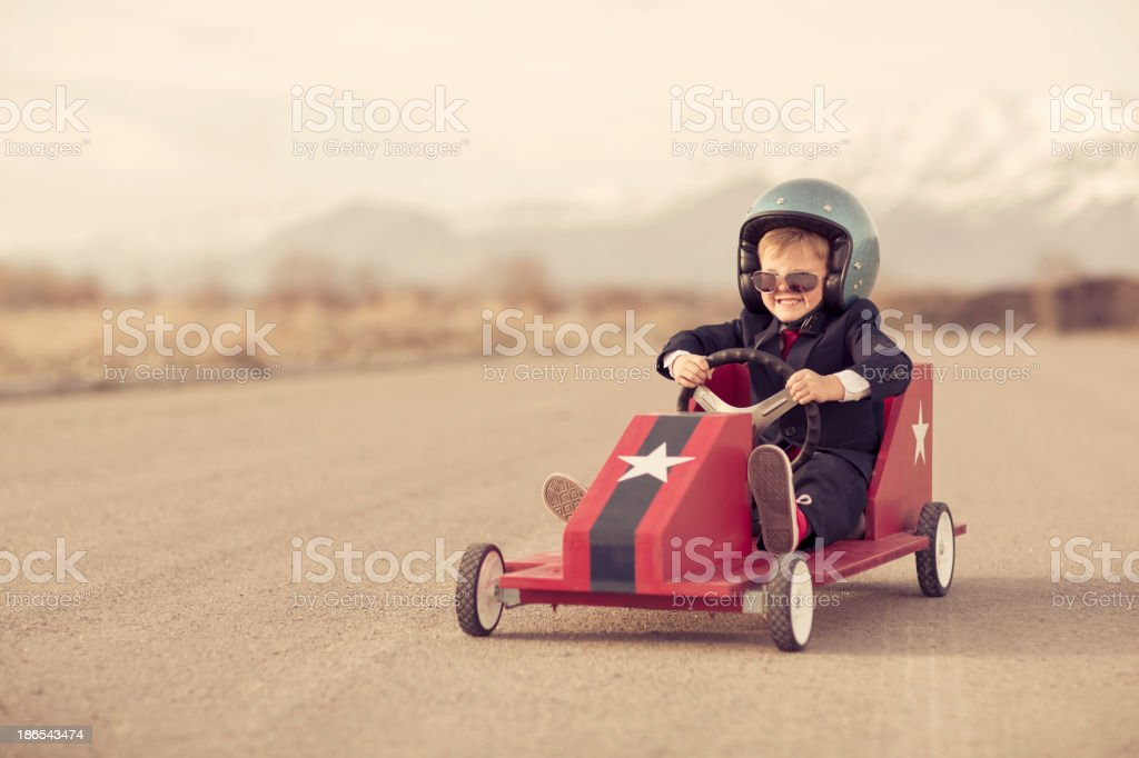 Young Boy Businessman Races Toy Car on Blacktop stock photo