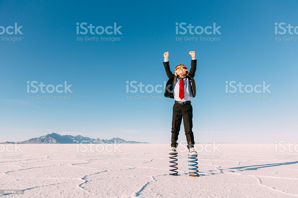 Young Boy Businessman Stands Arms Raised on Springs stock photo