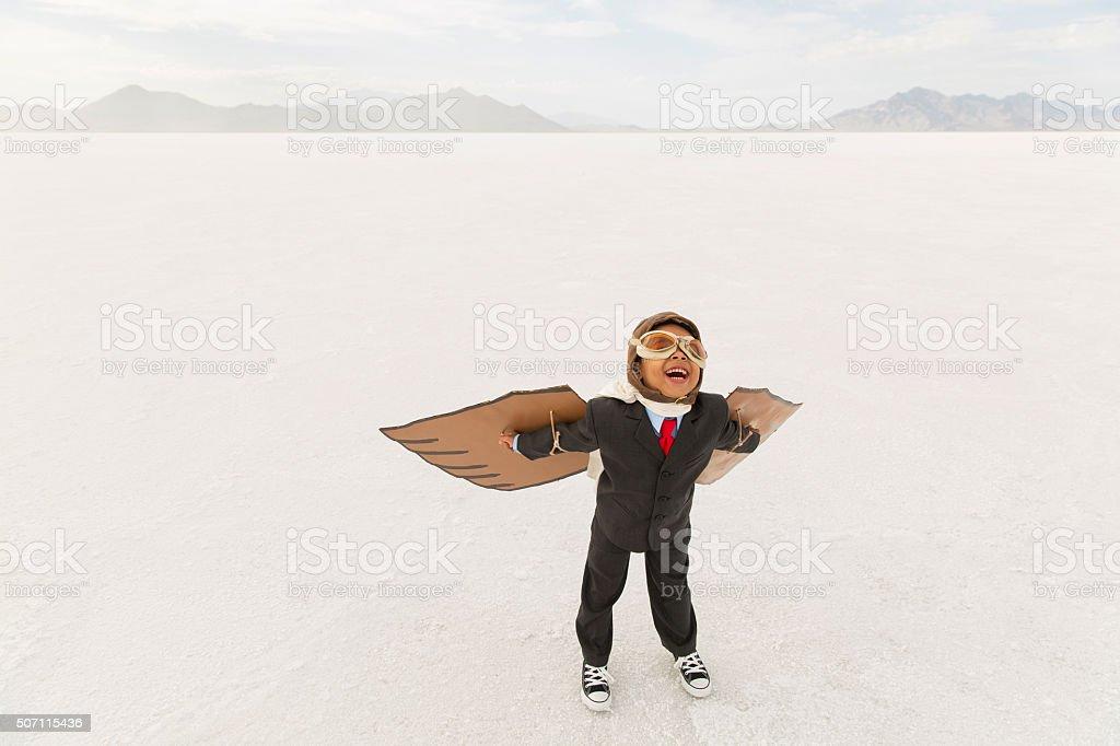 Young Boy Businessman Wearing Cardboard Wings stock photo